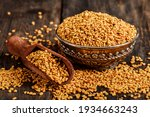 Small photo of Fenugreek seeds on metal plate, spice, culinary ingredient. Fenugreek seeds in wooden spoon on textured background. Fenugreek seeds in a spoon and on a table.