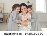 Small photo of Little kids learning to value money. Happy young single mother and two cute daughters holding piggy bank and smiling. Saving up for children's education, family finance, and budget management concept