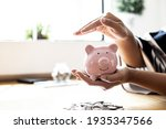 Small photo of A woman holding a piggy bank in the shape of a pink pig, she is organizing money to divide it into savings and buy funds to make it grow. Personal finance concept.