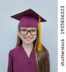 Small photo of Smiling Causation girl with glasses in a graduation gown and hat. White background. Graduation