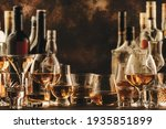 Small photo of Hard strong alcoholic drinks and distillates in glasses and bottles in assortment: vodka, cognac, tequila, scotch, brandy and whiskey, grappa, liqueur, vermouth, tincture, rum. Brown background
