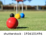 Small photo of In the foreground a red croquet ball is in close focus on a croquet lawn while the blue, yellow and black balls and the croquet hoop are out of focus in the background