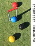 Small photo of Looking down onto a set of red, blue, black and yellow croquet balls and a croquet hoop with a red cross bar on a green croquet lawn on a sunny day