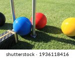 Small photo of A blue croquet ball is about to be struck with a croquet mallet through a croquet hoop to hit the red ball on a green croquet lawn with the yellow and black balls on either side