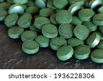 spirulina green pills on slate... | Shutterstock . vector #1936228306