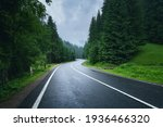 Road in foggy forest in rainy day in spring. Beautiful mountain curved roadway, trees with green foliage in fog and overcast sky. Landscape with empty asphalt road through woods in summer. Travel