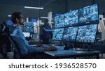 Small photo of Industry 4.0 Modern Factory: Security Operator Controls Proper Functioning of Workshop Production Line, Uses Computer with Screens Showing Surveillance Camera Feed. High-Tech Security