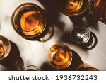 Small photo of Hard strong alcoholic drinks, spirits and distillates in glasses: vodka, cognac, tequila, scotch, brandy and whiskey, grappa, vermouth, rum. White background with hard lights and shadows, top view