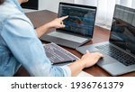 Small photo of Asian programmer woman pointing and looking on multiple laptop screen to writing code and database while working about development website or applications in software development office