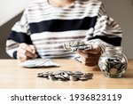 Small photo of Woman holding dollar bills, on the table a large pile of coins and banks, she is managing to divide the money to save money and invest it to make it grow even more. Saving money and investing concept.