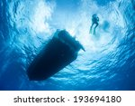A Scuba Diver Descends From A...