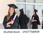 Small photo of group of graduates Asian student in academic gown and graduation cap holding diploma