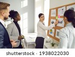 Small photo of Group of young diverse men and women listening to expert's advice in business workshop. Team manager pointing at column chart on bulletin board comparing sales performance in corporate office meeting