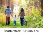 Stock photo family with dog walking in the forest back to camera 193802573