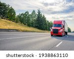 Small photo of Bright red diesel big rig industrial professional semi truck with black grille transporting commercial cargo in dry van semi trailer driving on the straight wide highway road with trees on hillside
