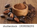 Small photo of Cocoa beans, powder, crushed cocoa beans and chocolate on wooden background.