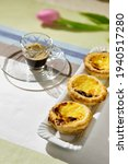 Small photo of three custards (Pasteis de nada) and an glassy espresso cup and a purple tulip are in the bokeh of the baclkdrop.