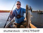 Small photo of Angler with Asp fish. Amateur fisherman holds the asp fish and stands in the boat with river on the background