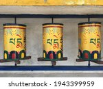 """A row of three yellow Tibetan Buddhist prayer wheels decorated with colourful symbols meaning """"Praise to the Jewel in the Lotus"""" on the path around the Dalai Lama temple in McLeodganj, India"""