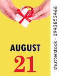 August 21st. Festive Vertical Calendar With Hands Holding White Gift Box With Red Ribbon And Calendar Date 21 August On Illuminating Yellow Background.Summer month, day of the year concept.
