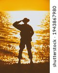 Silhouette of saluting commando soldier, army infantryman standing on shore during sunset or sunrise. Military solemn ceremony, respectable salute for honoring fallen heroes and comrades on seacoast