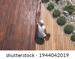 Small photo of Wood deck renovation treatment, the person applying protective wood stain with a brush, overhead view of ipe hardwood decking restoration process