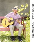 Old man with straw hat playing acoustic guitar on bench