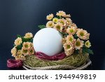 A Large Egg In A Nest Covered...