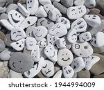 Small photo of Emotion management concept, stones with painted faces symbolize different emotions. We are all different, but all together, learning to manage emotions. Emotional intelligence, role model.