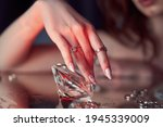 Small photo of Beauty Woman holds big diamond in hand while lying on table. Beautiful hands, professional manicure, large diamond brilliant