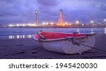 A boat on the beach at the end of the day after bad weather with the great mosque of Algiers and a big wheel in the background