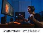 Small photo of Cybersport young pro gamer happy with winning the game, feel exited, show YES hand gesture, celebrates victory in online game competition. Side view. Guy playing video game at home in his room