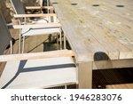 Small photo of Greyed Bangkirai wood and weathered teak furniture on a terrace