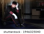 A Tired Doorman Sits On A...