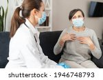 Small photo of Nurse in mask caring of senior female patient wearing mask at home during coronavirus pandemic. A mature woman complaints to doctor for feeling unwell, malaise. doctor's appointment at home