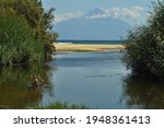 Small photo of A small and shallow river flows into the Aegean Sea on the Sithonia Peninsula.On the other side is the sacred Mount Athos.Half-salt wetland (brack or brackish water) with reeds.Holy mountain.