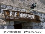 Small photo of Spiazzo, Trentino, Italy - July 07, 2020: Mandron Citta Di Trento refuge detail. Entrance to an alpine refuge with flat dark granite walls and wooden sign. White written in Italian: Mandron Refuge.