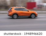 Small photo of Ukraine, Kyiv - 18 March 2021: Orange Nissan Rogue car moving on the street. Editorial
