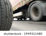 Small photo of A stationary car wheel against the background of a fast moving trailer. Speed concept. An example of contradistinction is immobility and movement.