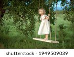 Small photo of A girl with light curly hair in a soft pink dress stands on a swing that is suspended from a tree and goes flying to and fro, to and fro