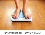 Stock photo female bare feet with weight scale on wooden floor 194974130