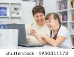 Small photo of Smiling girl with down syndrome is uses a laptop with her teacher at library. Education for disabled children concept
