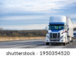 White big rig industrial semi truck transporting commercial cargo in dry van semi trailers driving in front of truck convoy on the wide multiline elevated interstate highway road