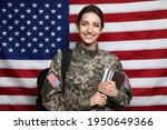 Female cadet with backpack and books against American flag. Military education