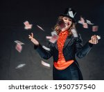 Small photo of Funny female rogue from circus poses with flying cards in dark background