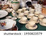 Small photo of Antiques on flea market or festival - vintage porcelain tea cups, tableware and other vintage things. Collectibles memorabilia and garage sale concept. Selective focus
