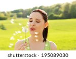 Woman Blowing On A Dandelion.
