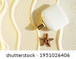 Small photo of white perfume bottle on a sandy textured background with seafish. Summer scent concept for vacation