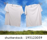Stock photo white t shirt hanging on outdoor clothesline with blank front ready for logo or message 195123059