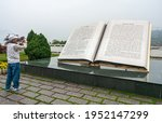 Small photo of Three Gorges Dam, China - May 6, 2010: Yangtze River. Giant book statue with explanatory text about Tanziling Ridge. Man takes picture on side of green foliage and yellow flowers under foggy morning s